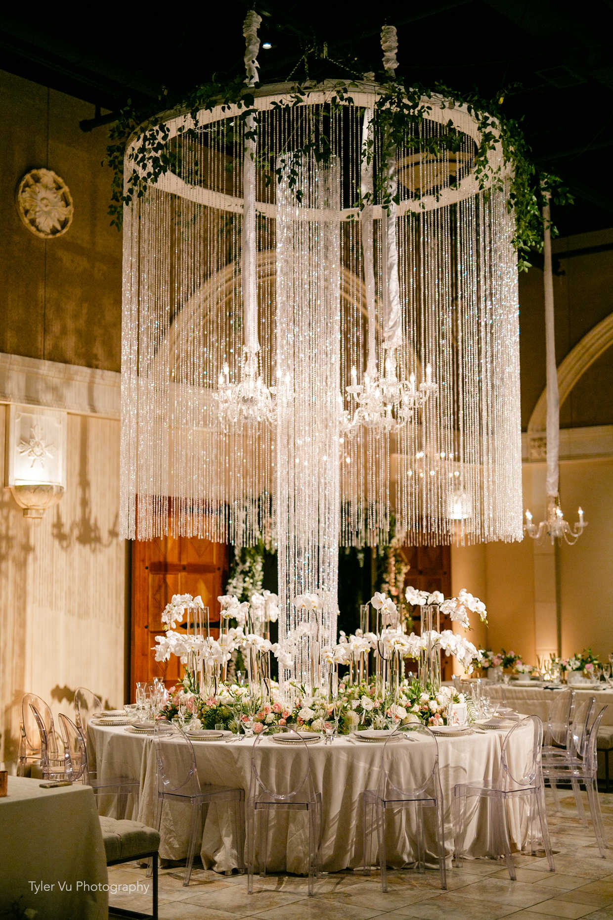 Stunning wedding reception table with overhead chandelier and orchid centerpieces at Casa Real at Ruby Hill Winery (www.casarealevents.com).  Photo by: Tyler Vu Photography; Florals and Design: Nicole Ha Design; Lighting: Fantasy Sound Event Services; Chairs: Pleasanton Rentals