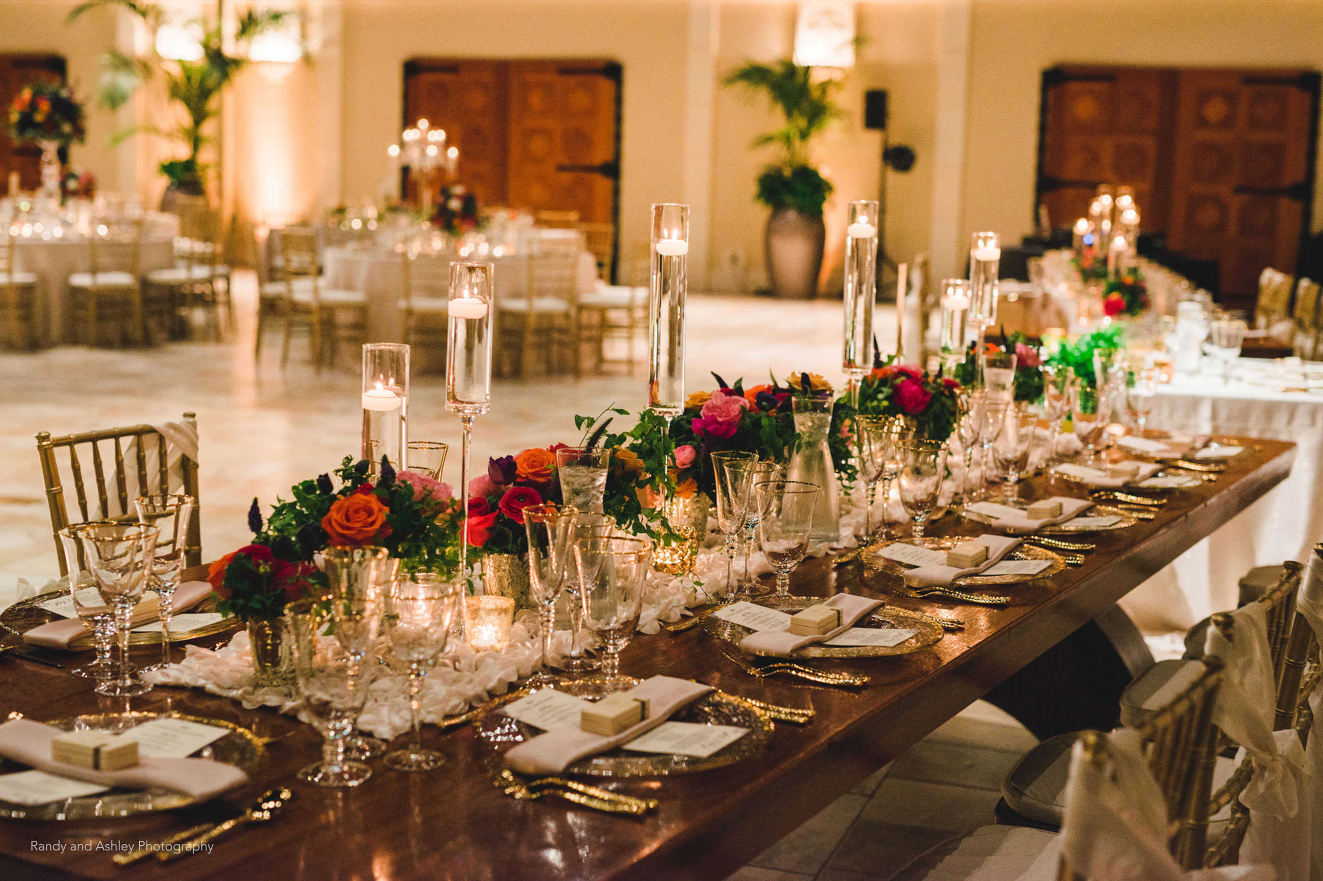 Elegant candlelit wedding reception table with gold and roses at Casa Real at Ruby Hill Winery (www.casarealevents.com).  Photo by: Randy and Ashley Photography; Florals: Enchantment Floral; Linens: Napa Valley Linen; Glassware, Flatware and Chargers: Pleasanton Rentals